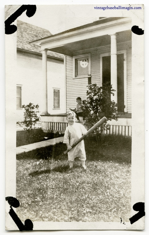 Small boy with big basebal bat poses in front yard, circa 1920s old photo