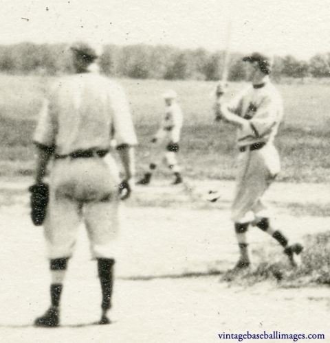Detail of a section of a vintage snapshot of an early rural baseball game, showing the batter's grip